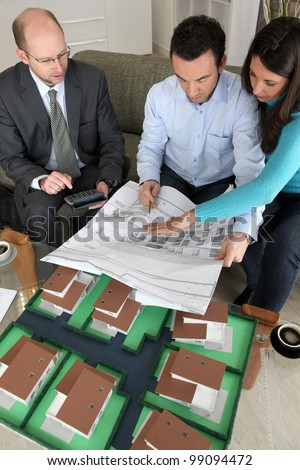 Young couple looking over new house plans - stock photo