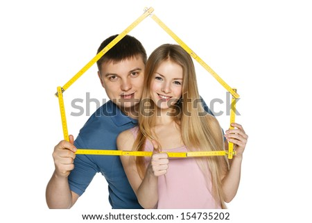 Young couple looking through the house frame, over white background - stock photo