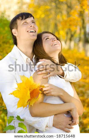 young couple looking up in autumn park - stock photo