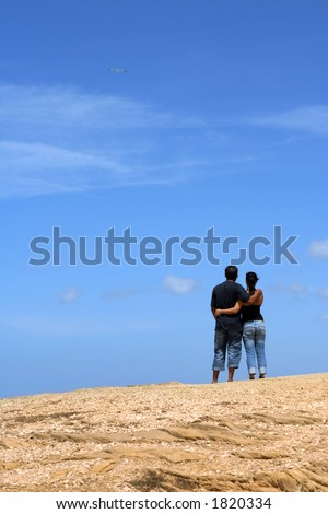 Young couple looking up together with sky background - stock photo