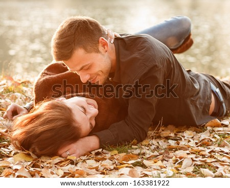 young couple lying down near lake smiling having good time - stock photo