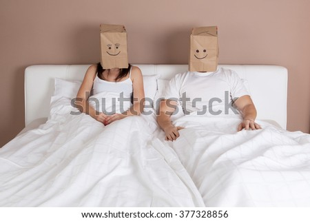 young couple lying in bed with paper bags over heads - stock photo
