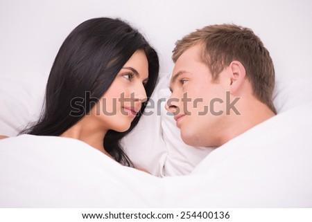 Young couple lying in white bed early in the morning under white blanket and looking at each other