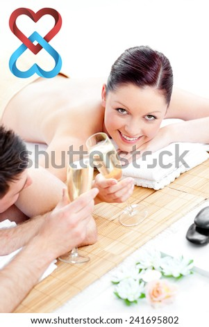 Young couple lying on a massage table and drinking champagne against linking hearts - stock photo