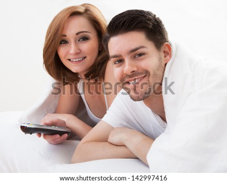 Young couple lying on mattress watching television - stock photo