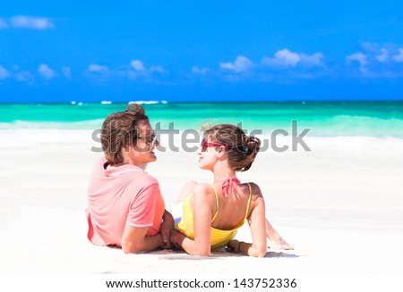 young couple lying on sand under sunny summer sun - stock photo