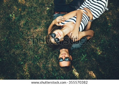 Young couple lying on the grass with sunglasses on sunny day - stock photo