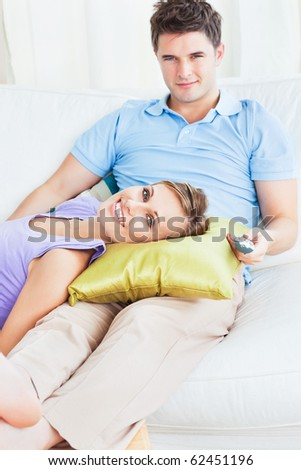 Young couple lying on the sofa at home - stock photo