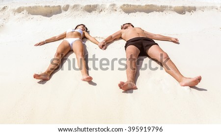 Young couple lying on the white sands holding hands