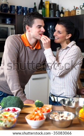 Young couple making and tasting vegetable salad