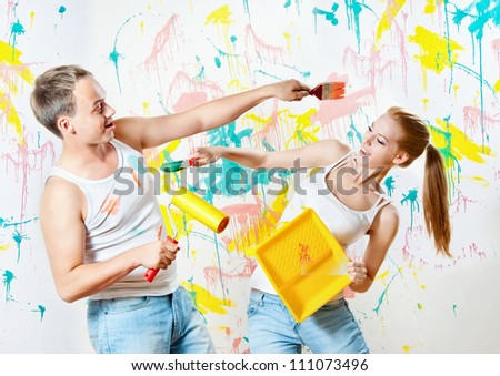 Young couple making repairs in the paint - stock photo