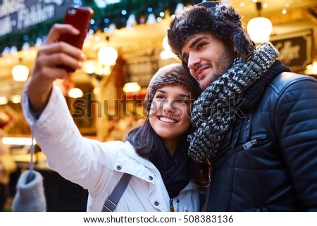 Young couple making selfie on christmas market, smiling happy.