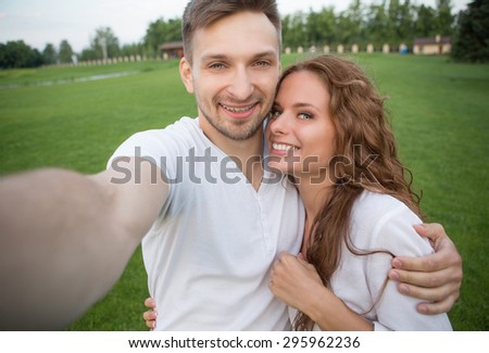 Young couple making selfies in the sunset. Man and woman in love enjoying day time in the countryside. - stock photo