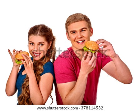 Young couple man and woman back to back and eating hamburgers  . Fastfood concept.  Isolated. - stock photo