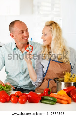 Young couple - man and woman - cooking in their kitchen at home
