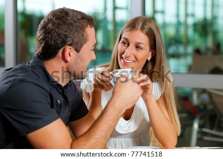 Young couple - man and woman - drinking coffee in a cafe in front of a glass facade - stock photo
