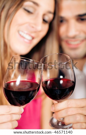 Young couple - man and woman - in a restaurant clinking the red wine glasses; focus on the glasses - stock photo