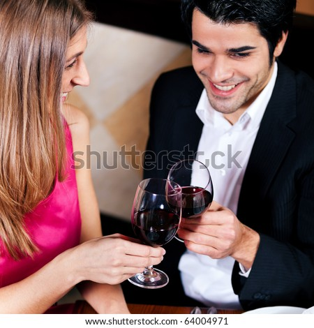 Young couple - man and woman - in a restaurant drinking glasses of red wine - stock photo