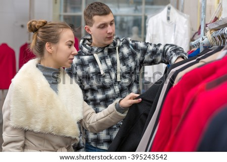 Young Couple Man and Woman looking at variety of Jackets at Clothing Retail Store
