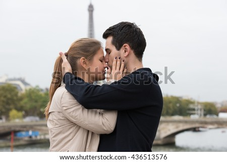 young couple man and woman sitting on the bridge on river Seine, Paris, France, in front of Eiffel Tower, kissing
