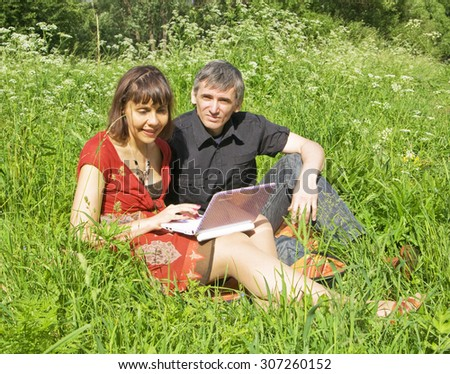 Young couple man and woman with notebook computer on grass meadow. - stock photo