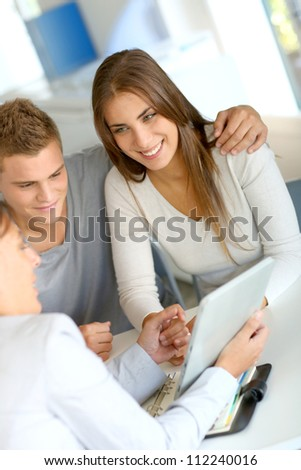 Young couple meeting financial consultant for credit loan - stock photo