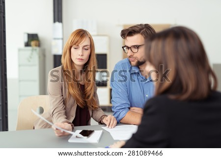 Young couple meeting with their investment broker discussing a document with her during the presentation, view over the agents shoulder - stock photo