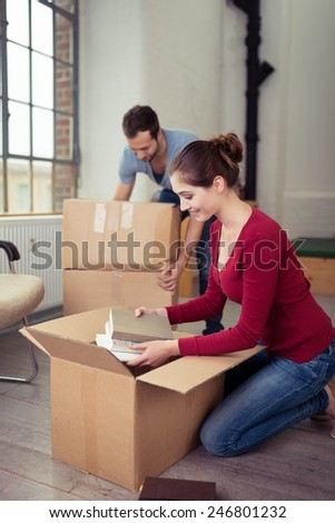 Young couple moving house busy in the living room packing or unpacking cardboard boxes with books and personal possessions - stock photo