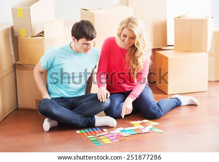Young couple moving in a new home. Wife and husband selecting a new color for a condo. - stock photo