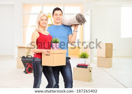 Young couple moving into a new apartment full of moving boxes - stock photo
