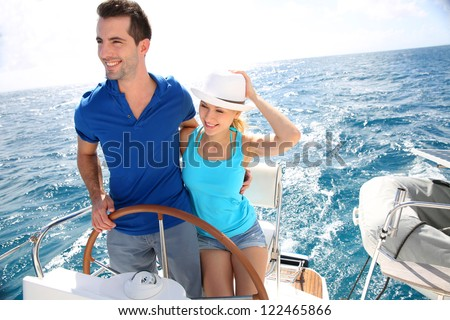 Young couple navigating on a yacht in caribbean sea - stock photo