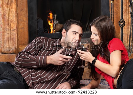Young couple near fireplace holding glass of wine - stock photo