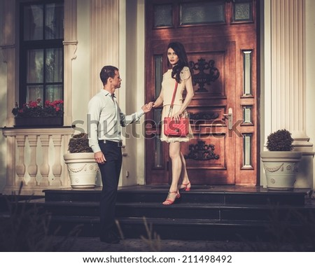 Young couple near luxury home entrance  - stock photo