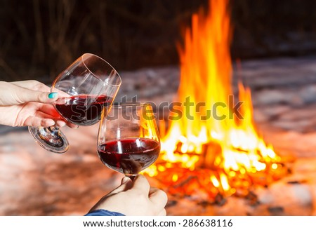 Young couple near the bonfire with two glasses of red wine - stock photo