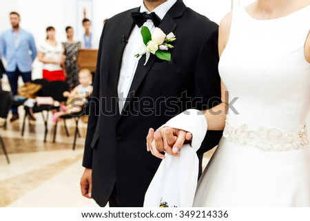 Young couple newlyweds in front of the altar in the church. Wedding process of men and women in wedding dress.