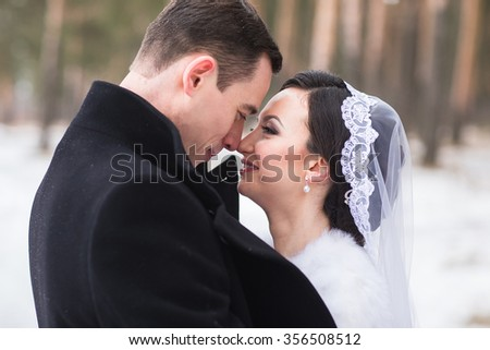 Young couple newlyweds walking in a winter forest in the snow. Bride and groom hugging in the park in winter. Beautiful man and woman in their wedding clothes are among the pines. - stock photo