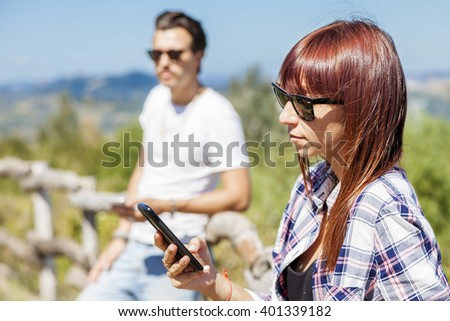 young couple of adults writes on their mobile phone - stock photo