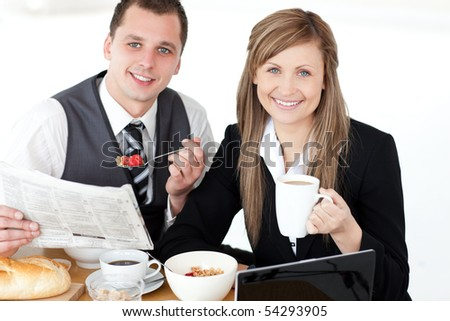 Young couple of business people reading a newspaper while having breakfast at home