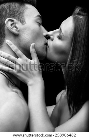Young couple of lovers kissing on black background - stock photo