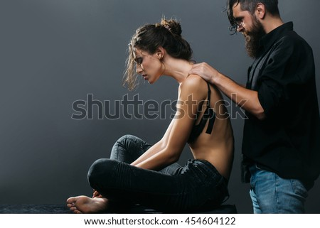 young couple of pretty sexy woman in black jeans and bra has slim body and handsome bearded man with long beard in shirt doing massage on grey background, copy space