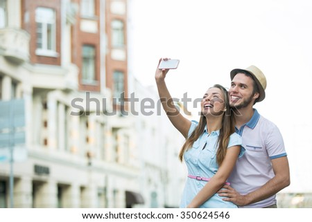 Young couple of tourists make selfie - stock photo