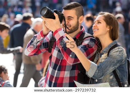 Young couple of travellers with photocamera and map at street