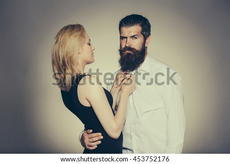 young couple of woman with pretty face and blonde hair in black vest and handsome bearded man with long beard in white shirt in studio on grey background