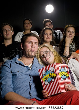 Young couple on a date at the movie theater - stock photo
