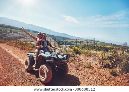 Young couple on an off road adventure. Man driving quad bike with girlfriend sitting behind and enjoying the ride in nature. - stock photo