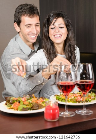 Young couple on anniversary date. Young Man and woman smiling and cooking together, preparing a romantic dinner. - stock photo