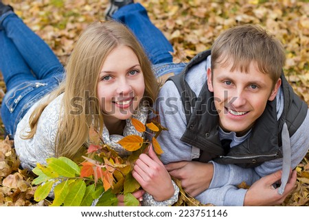 Young couple on leaves  in the autumn park - stock photo