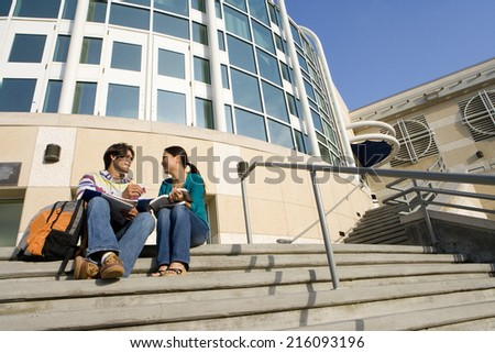 Young couple on steps studying, low angle view - stock photo