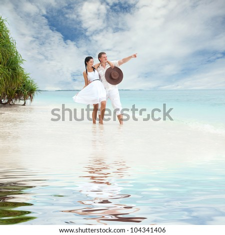 Young couple on the beach of sea - stock photo