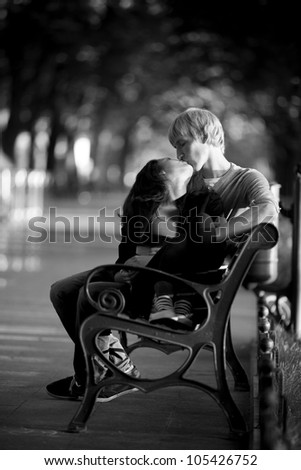 Young couple on the bench at the street. Photo in black and white style. - stock photo